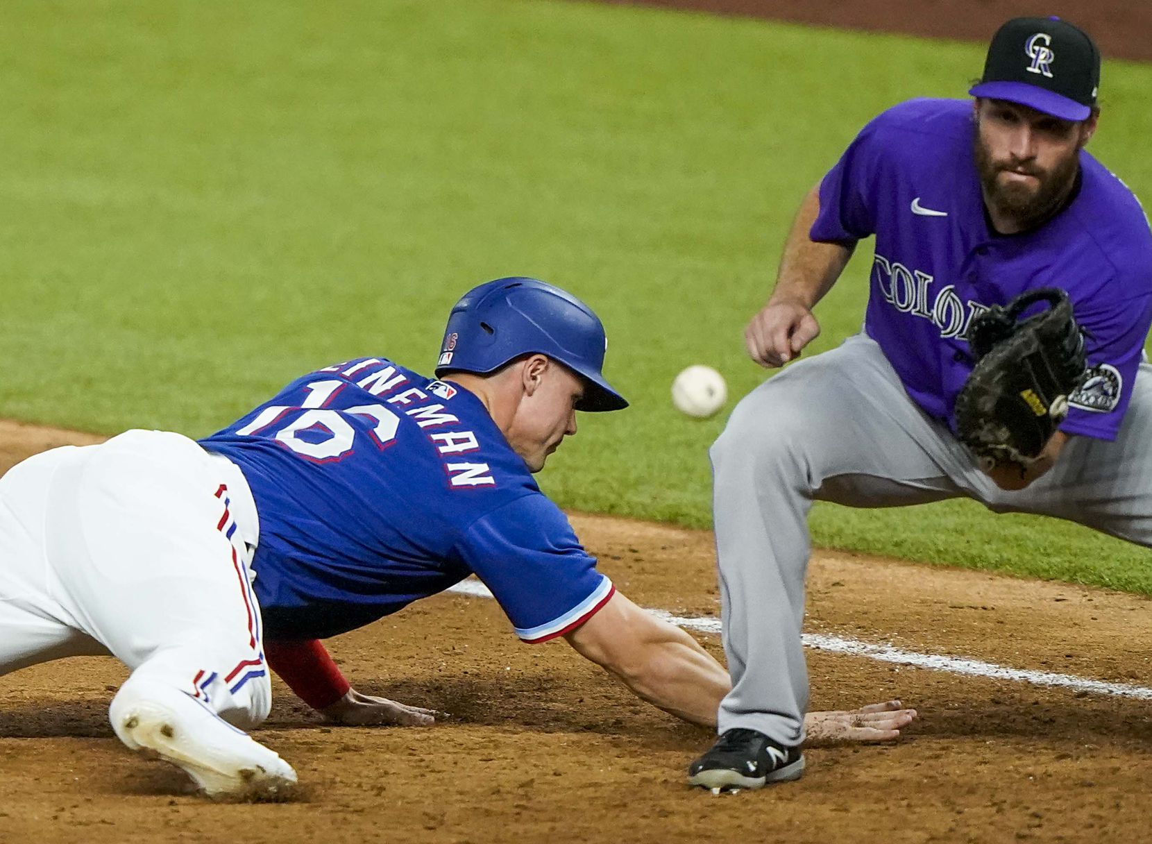 Texas Rangers outfielder Scott Heineman gets back to first base on a pickoff attempt ahead of the throw to Colorado Rockies first baseman Daniel Murphy during the fifth inning of an exhibition game at Globe Life Field on Tuesday, July 21, 2020.