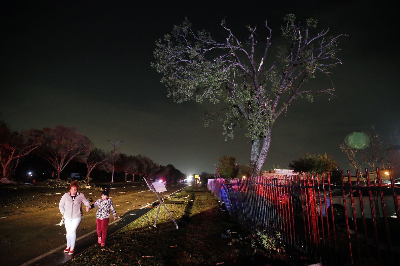People walk along the debris strewn Pioneer Parkway in Arlington after a tornado-warned storm tore the roofs off The Mirage Apartments, Tuesday night, November 24, 2020. Air conditioner units and other structural debris were scattered across the property and street.