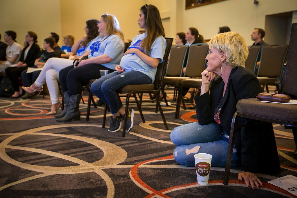 Environmental activist Erin Brockovich sits on the floor and listens as water consultant Bob Bowcock addresses a town hall style meeting at Frisco Celebration Hall on Thursday.