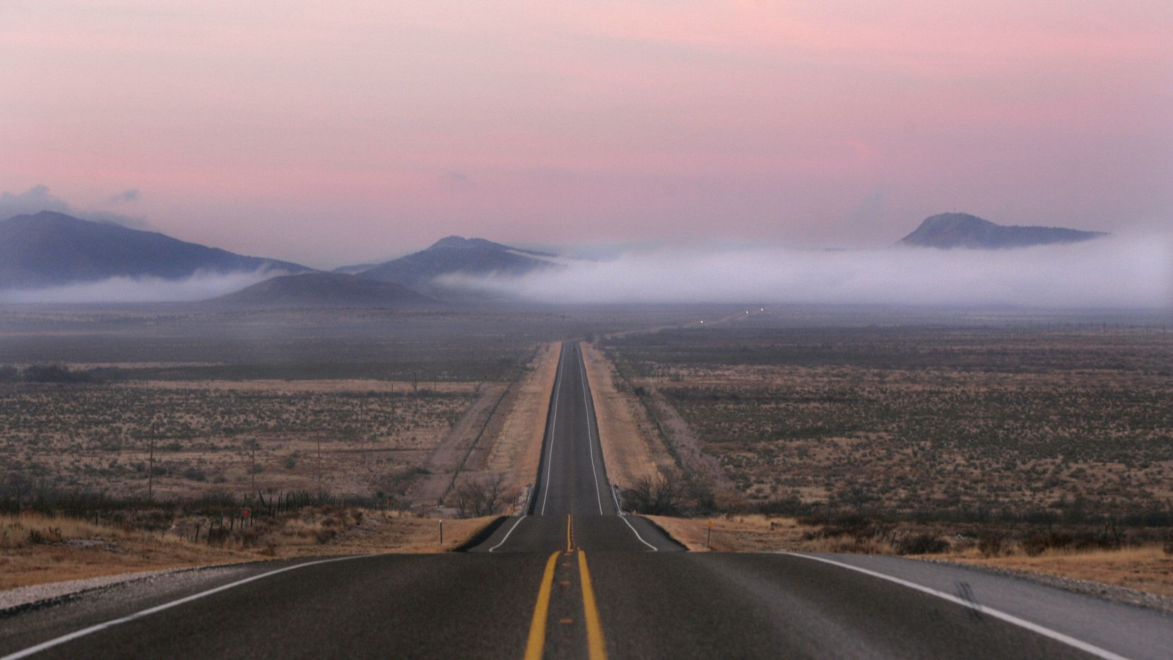 This file photo shows a pink sky and low-lying clouds on a highway just east of Alpine in far West Texas. Some pregnant women already travel an hour and a half or longer to reach the 25-bed Big Bend Regional Medical Center in Alpine, which serves a swath that extends southwest to the Mexican border and includes Big Bend National Park as well as the communities of Presidio and Candelaria.