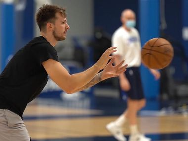Dallas Mavericks guard Luka Doncic catches the ball during the team's mandatory workout on Thursday, July 2, 2020, as coach Rick Carlisle looks on. The team began workouts this week since the coronavirus pandemic halted all NBA play.