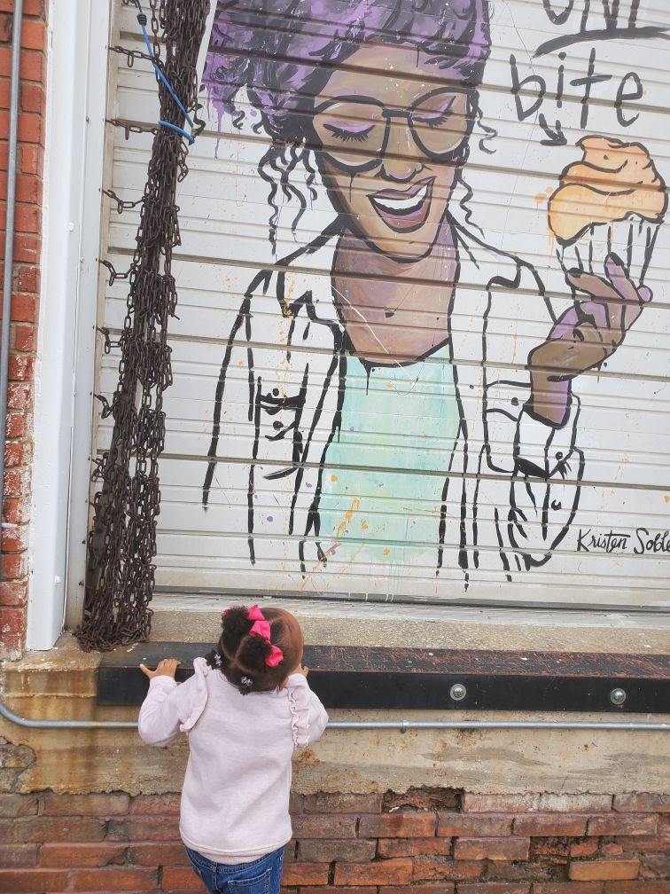A girl looks up at a mural by Kristen Soble of Tareka Lofton outside of her bakery, Loft 22 Cakes, in Fort Worth. One of Tareka's goals is to mentor young women of color, show them that they can achieve their dreams with enough hard work and commitment.