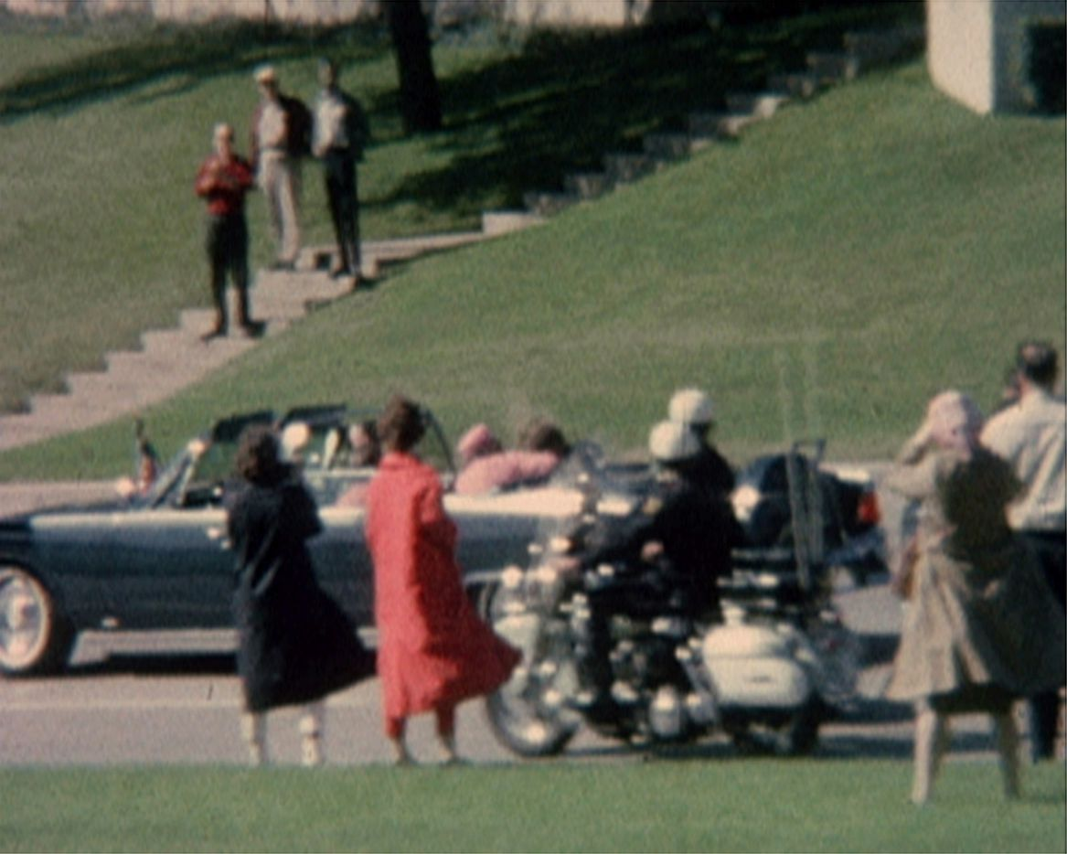 First lady Jacqueline Kennedy (in pink) cradles her husband Pres. John F. Kennedy seconds after he was fatally shot  in Dallas on Nov. 22, 1963.