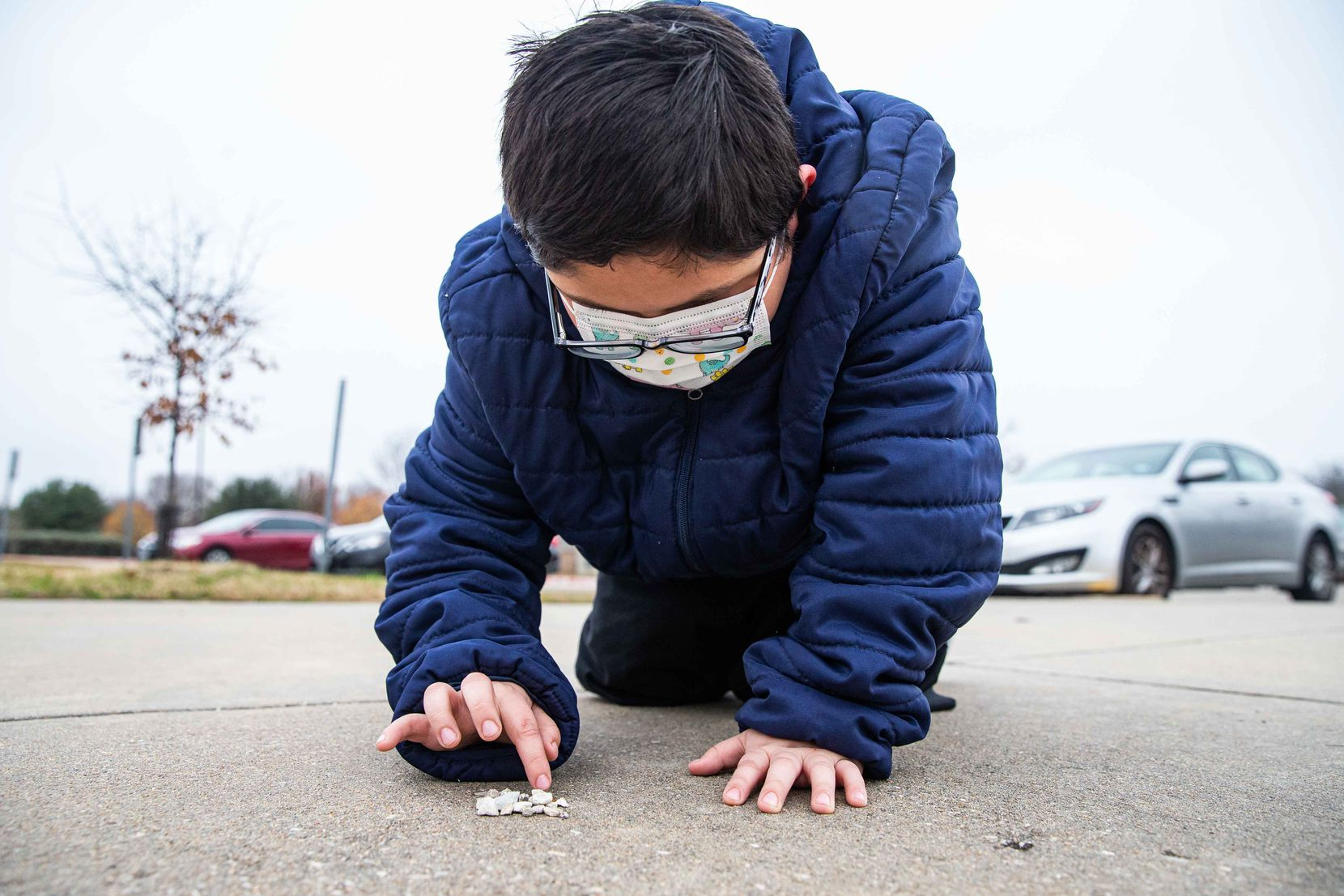 David Sanroman, 7, counts some rocks that he picked up from the ground at Frank Guzick Elementary School in Dallas on Tuesday, December 15, 2020. His mother Rosa Mendoza says that Sanroman has thrived since returning to in-person school after  months of learning virtually.