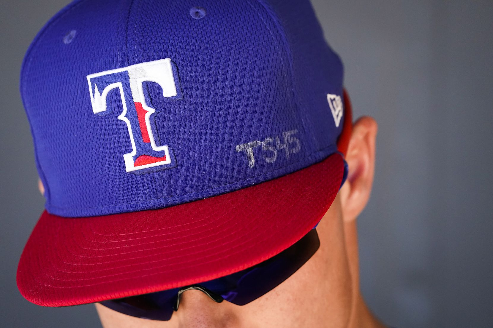 Texas Rangers outfielder Scott Heineman wears the initials of late Los Angeles Angels pitcher Tyler Skaggs on his hat before a spring training game against the Colorado Rockies at Salt River Fields at Talking Stick on Wednesday, Feb. 26, 2020, in Scottsdale, Ariz.