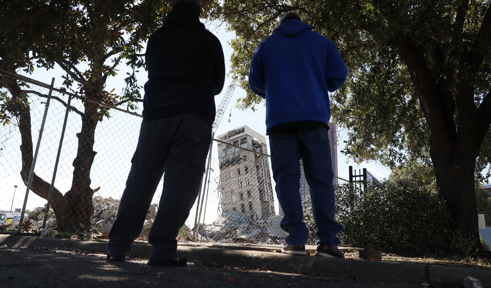 """People gather to watch the demolition of the so called """"Leaning Tower of Dallas"""" as a wrecking ball works to topple the structure north of downtown Dallas, Monday, Feb. 24, 2020. The still standing structure is part of an 11-story building that found a second life online after surviving a first demolition attempt. The former Affiliated Computer Services building inspired jokes and comparisons to Italy's Leaning Tower of Pisa when a Feb. 16 implosion failed to bring down its core. The company that engineered the blast said some explosives did not go off. (AP Photo/LM Otero)"""