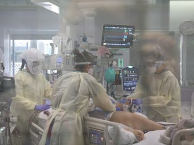 Nurses care for a child with COVID-19 in Cook Children's intensive care unit.