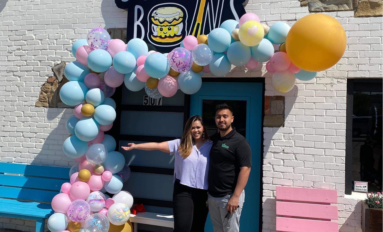 Zoya and Gerardo Hernandez stand in front of newly opened Scoop N' Buns on April 20, 2021.