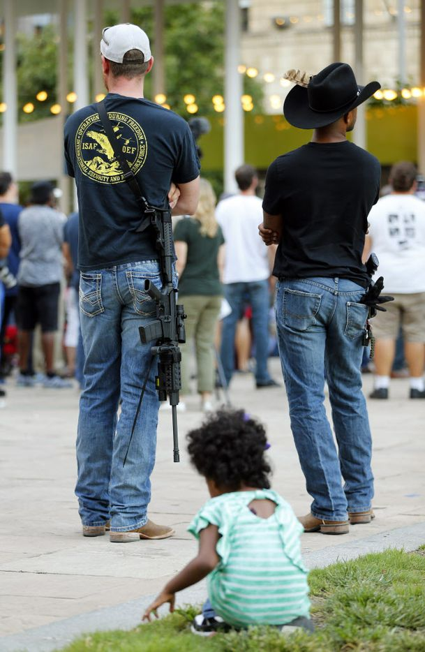 A young girl plays in the grass near a couple of 2nd Amendment supporters who attended the Next Generation Action Network protest in Main St. Garden Park downtown Dallas, Thursday, September 22, 2016. In response to the police killings, the group is standing in solidarity with the families and all of those who want justice for all. (Tom Fox/The Dallas Morning News)