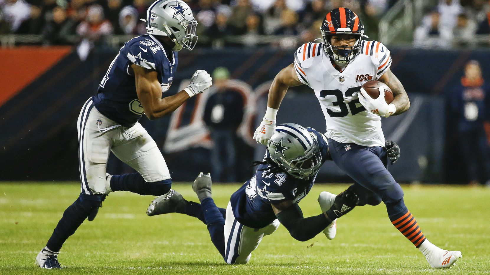 Dallas Cowboys middle linebacker Jaylon Smith (54) and cornerback Byron Jones (31) work to stop Chicago Bears running back David Montgomery (32) during the first half a NFL matchup between the Dallas Cowboys and the Chicago Bears on Thursday, Dec. 5, 2019, at Soldier Field in Chicago. (Ryan Michalesko/The Dallas Morning News)