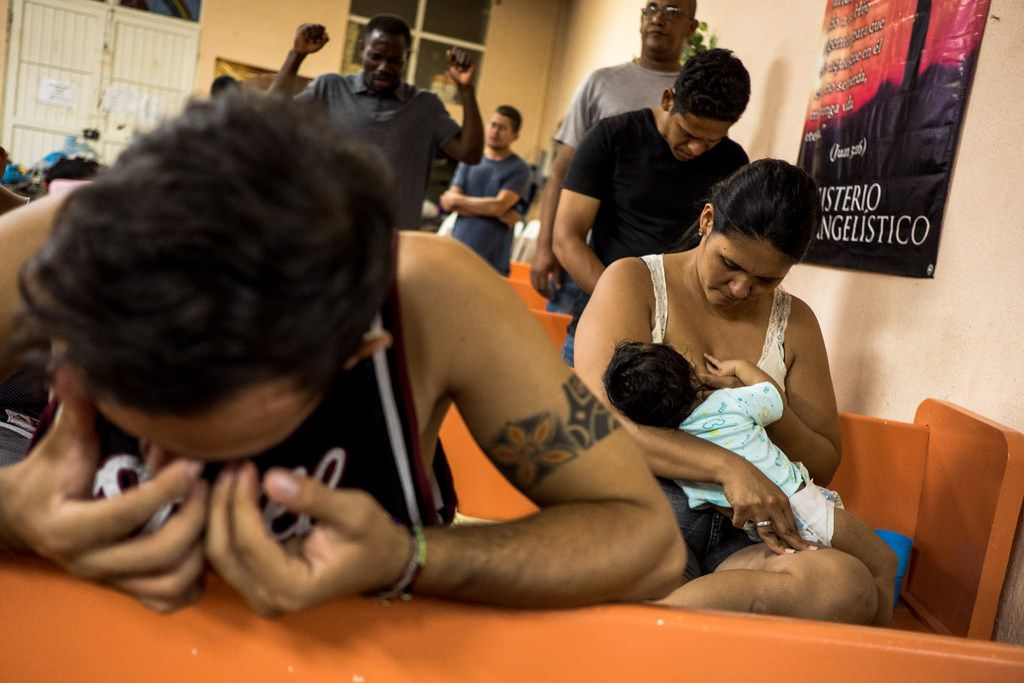 Joseph Banegas, 26, left, wipes tears from his eyes during a prayer as his wife Endira Rodriguez, 27, right, breastfeeds their four-month-old son Joseph Jr., at the El Buen Pastor migrant shelter in Ciudad Juâ¡rez, Chihuahua, Mexico, on Thursday, Aug. 1, 2019. The family fled violence in their home-country of Honduras and are waiting in Juarez for their U.S. asylum case to be processed.