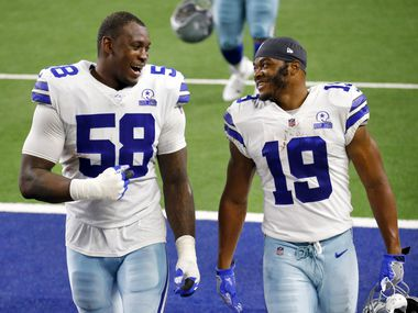 Dallas Cowboys defensive end Aldon Smith (58) and wide receiver Amari Cooper (19) laugh as they walk off the field following their game against the Pittsburgh Steelers at AT&T Stadium in Arlington, Texas Sunday, November 8, 2020.
