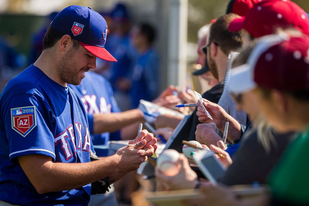 Texas Rangers pitcher Matt Moore signs autographs during a spring training workout at the team's training facility on Sunday, Feb. 18, 2018, in Surprise, Ariz. (Smiley N. Pool/The Dallas Morning News)