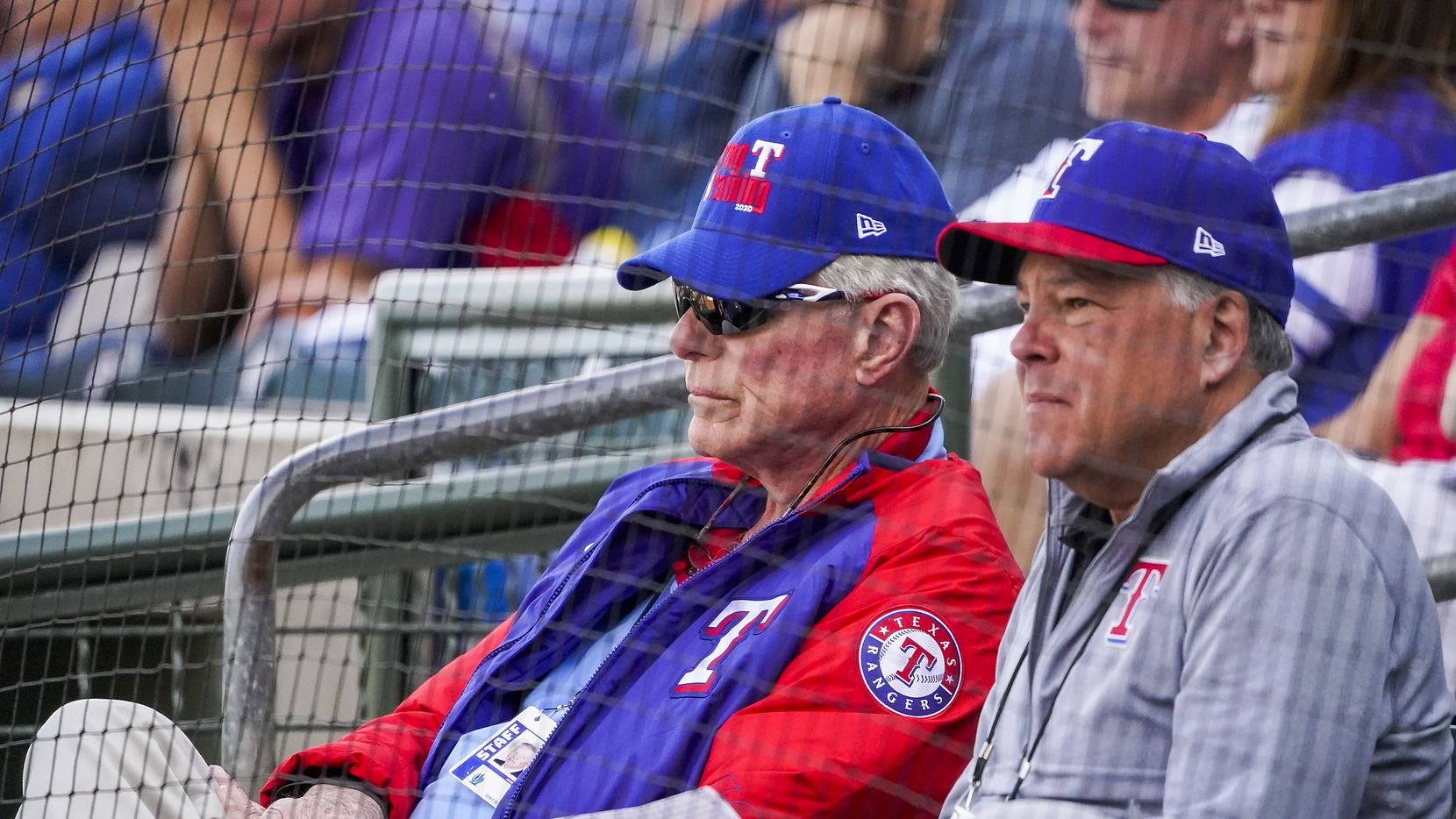 FILE — Texas Rangers co-chairman and managing partner Ray C. Davis (left) and chairman, ownership committee and chief operating officer Neil Leibman watch during the third inning of a spring training game against the Chicago Cubs at Surprise Stadium on Thursday, Feb. 27, 2020, in Surprise, Ariz.