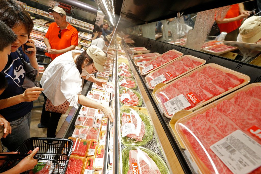 Monica Tse looks through the meat section of the butchers during the grand opening of the Mitsuwa Market place in Plano, Texas on April 14, 2017. (Nathan Hunsinger/The Dallas Morning News)