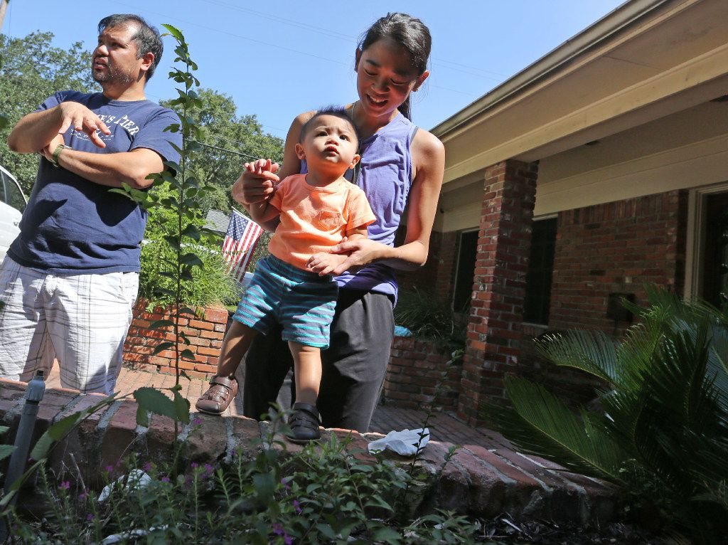 Troy and Catherine Pham and 13-month-old Aidan survey the scene as cleanup continues on the street where they live in the Meyerland section of Houston.