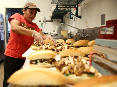 Rosalinda Domingo made grilled Latin chicken sandwiches at Pollo Campero, a Latin American chicken restaurant, in Dallas on Tuesday. (Rose Baca/The Dallas Morning News)