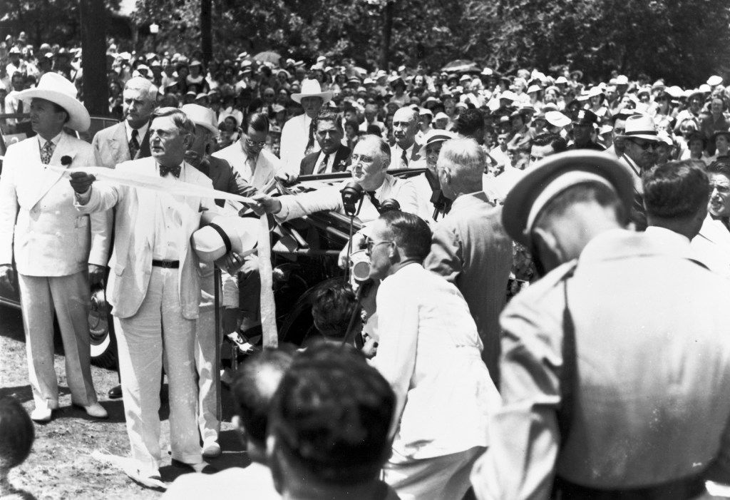 President Franklin D. Roosevelt seated in an automobile as he pulls a ribbon to unveil the statue of Robert E. Lee at Lee Park in Dallas, Texas, on June 12, 1936. Pres. Roosevelt also spoke at the Texas Centennial Exposition, at Fair Park, earlier in the day.