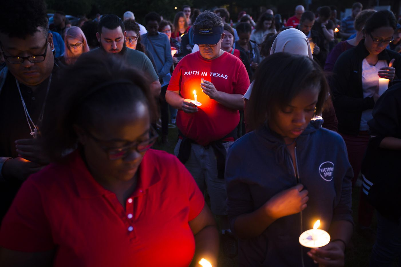 """Attendees try to keep their candles lit against the wind during the """"Remember His Name: Vigil for Jordan Edwards"""" candlelight vigil at Virgil T. Irwin Park on Thursday, May 4, 2017, in Balch Springs, Texas."""