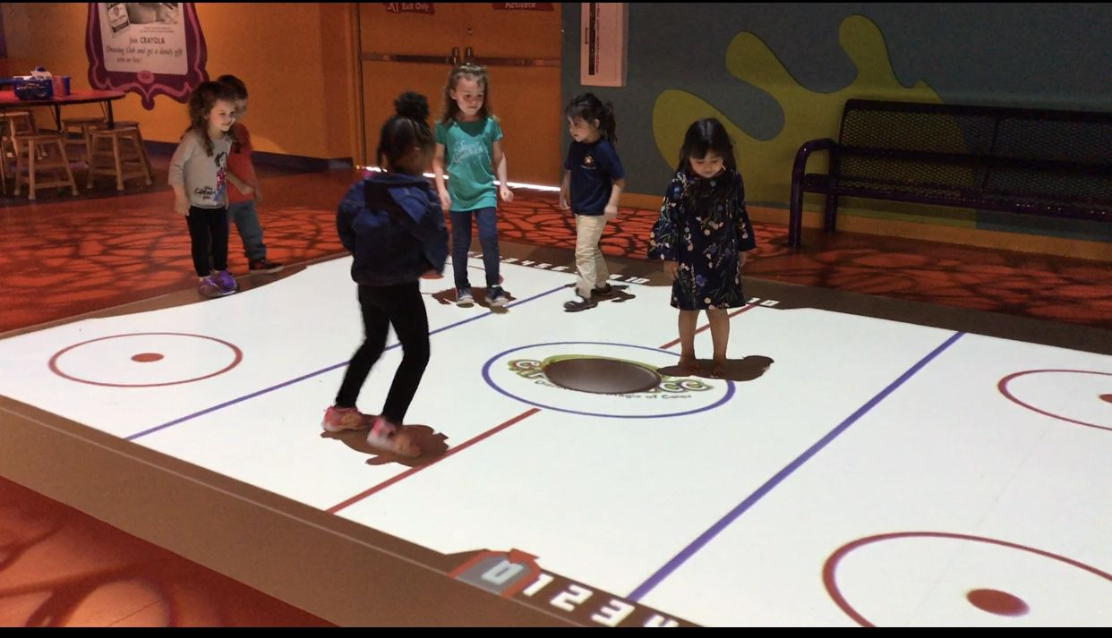 Kids play a game of air hockey in the Stomp and Play station during the grand opening of the Crayola Experience in Plano.