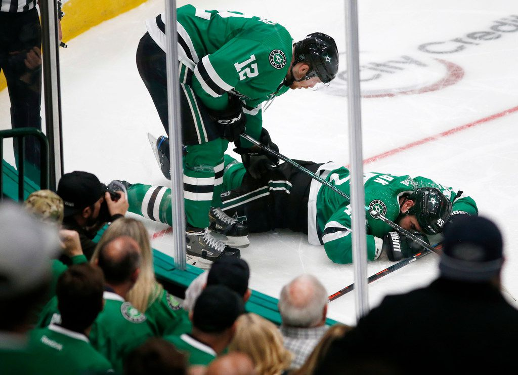 Dallas Stars center Radek Faksa (12) checks on injured player Dallas Stars defenseman Roman Polak (45) during the second period of play in the home opener at American Airlines Center in Dallas, Thursday, October 3, 2019.