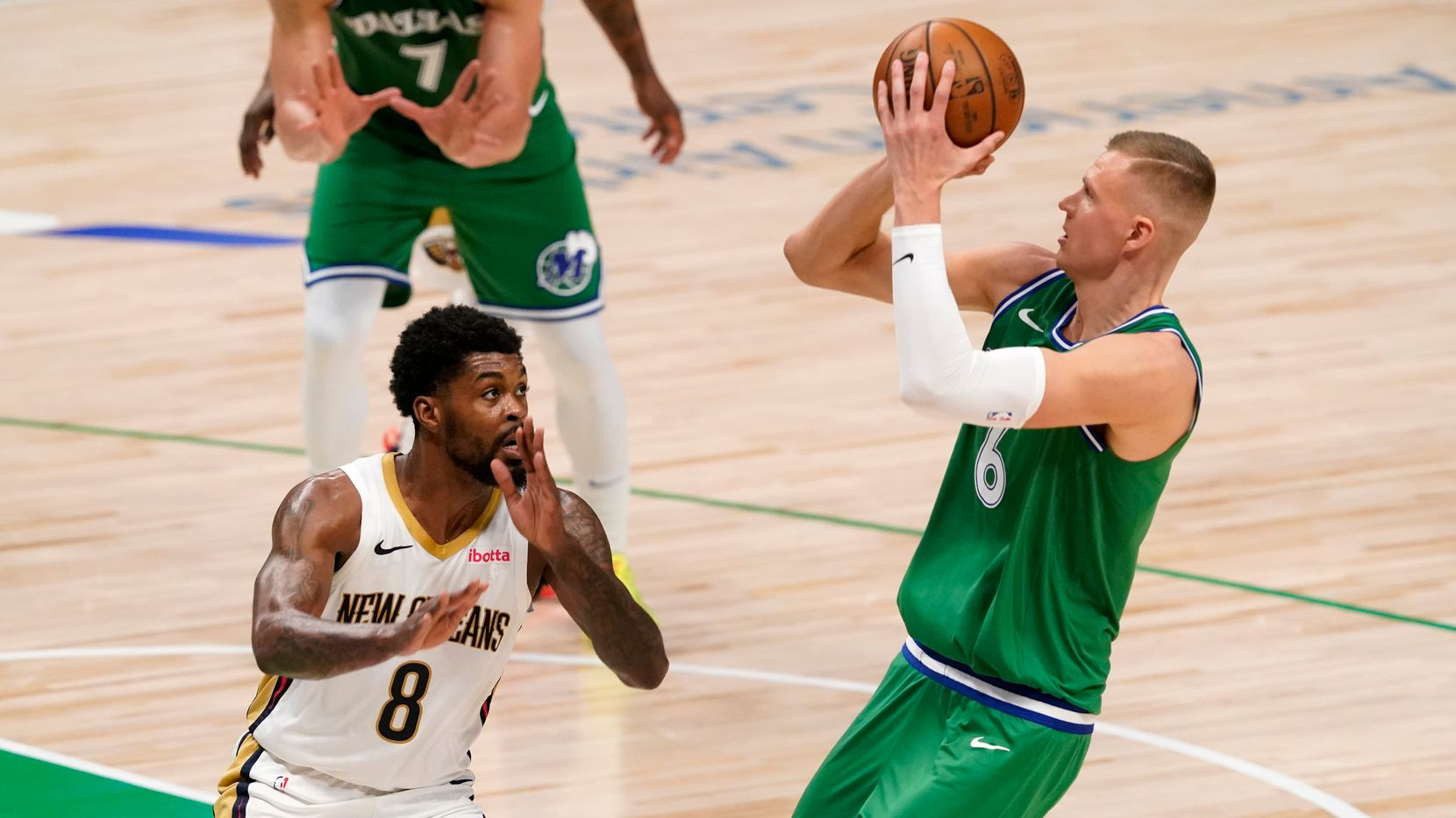 New Orleans Pelicans' Naji Marshall (8) defends as Dallas Mavericks center Kristaps Porzingis (6) shoots during the first half of an NBA basketball game in Dallas, Wednesday, May 12, 2021. (AP Photo/Tony Gutierrez)