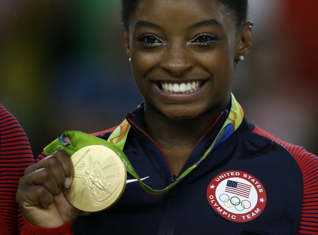 United States' Simone Biles displays her gold medal for floor during the artistic gymnastics women's apparatus final at the 2016 Summer Olympics in Rio de Janeiro, Brazil, Aug. 16, 2016. (AP Photo/Rebecca Blackwell)
