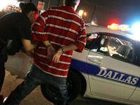 Un agente de la policía de Dallas detiene a una persona que no respetó la hora de toque queda en el centro de la ciudad, el lunes.