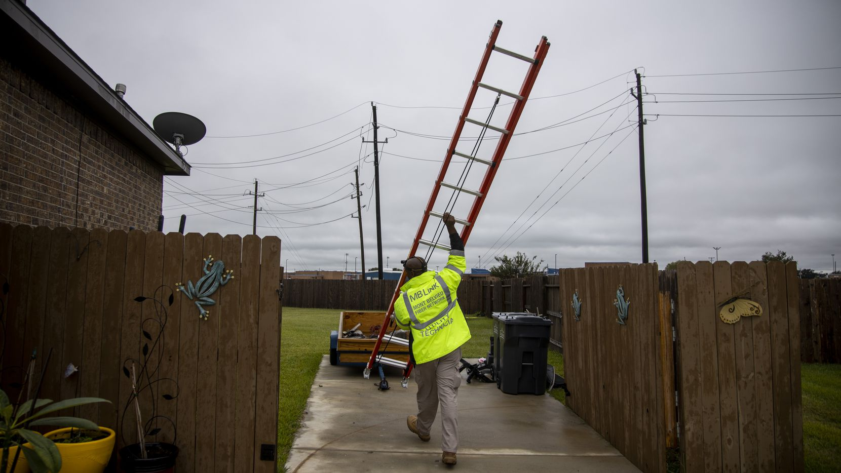 O'Neal Young, broadband installation technician for MB Link, carries a ladder as he works on installing internet for a new customer.  (Shaban Athuman/Staff Photographer)