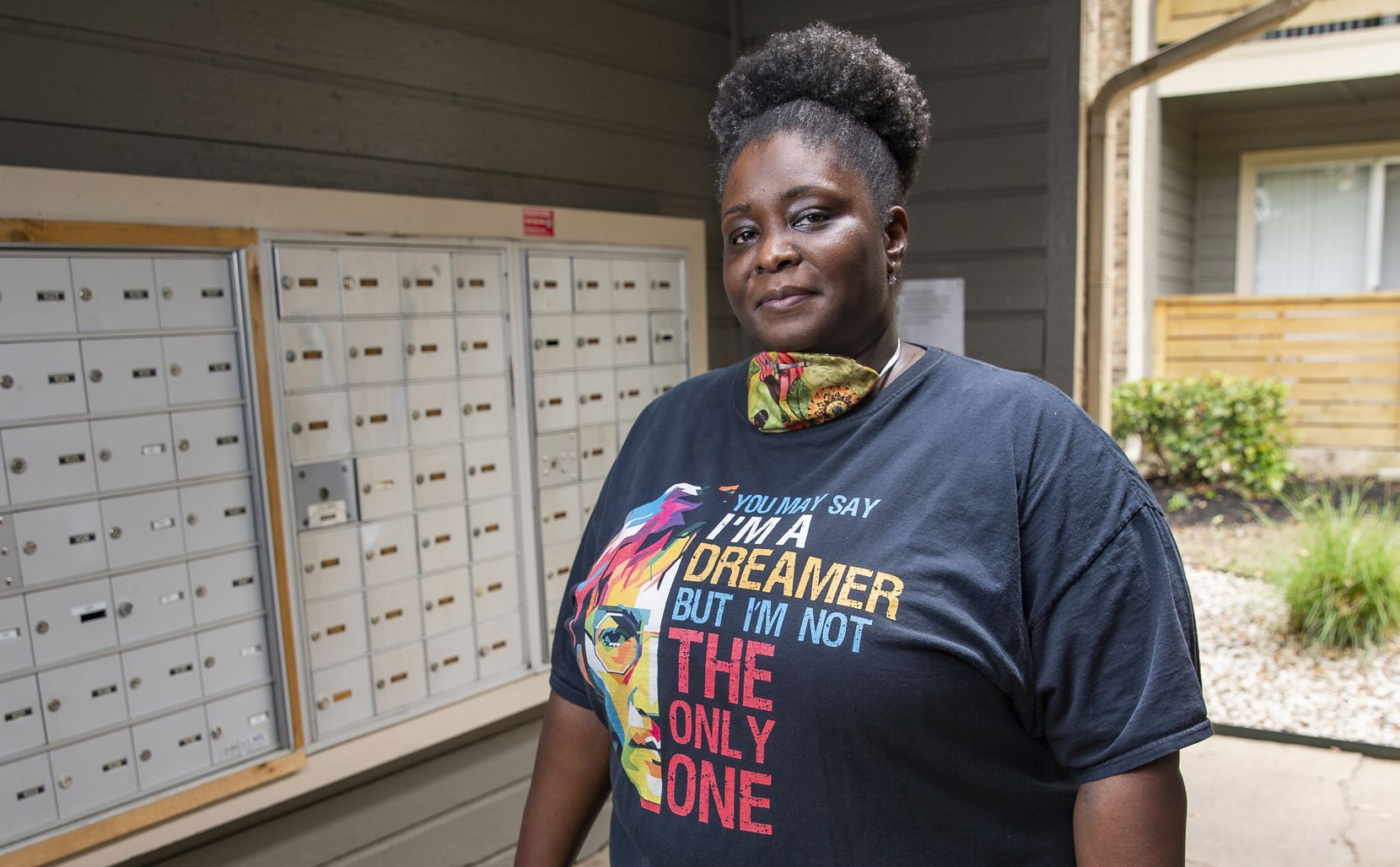 Katina Range, who has worked as a postal clerk since 1992, poses for a photo in the mail center at her apartment complex in Dallas.