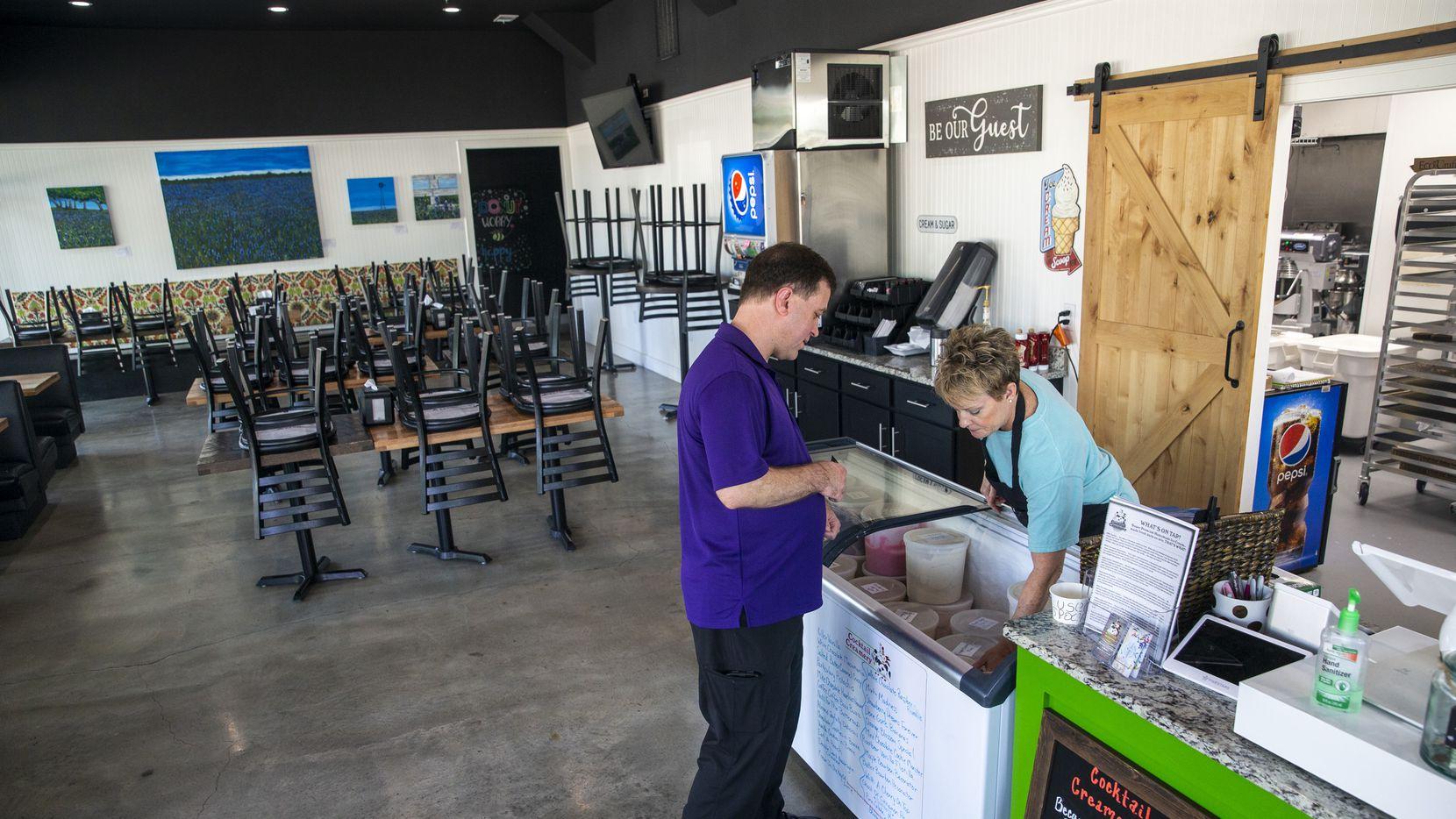 Donut Kitchen employee Julie Davidson (right) helped McKinney resident Paul Giles choose a sweet treat on Thursday, March 26, 2020.