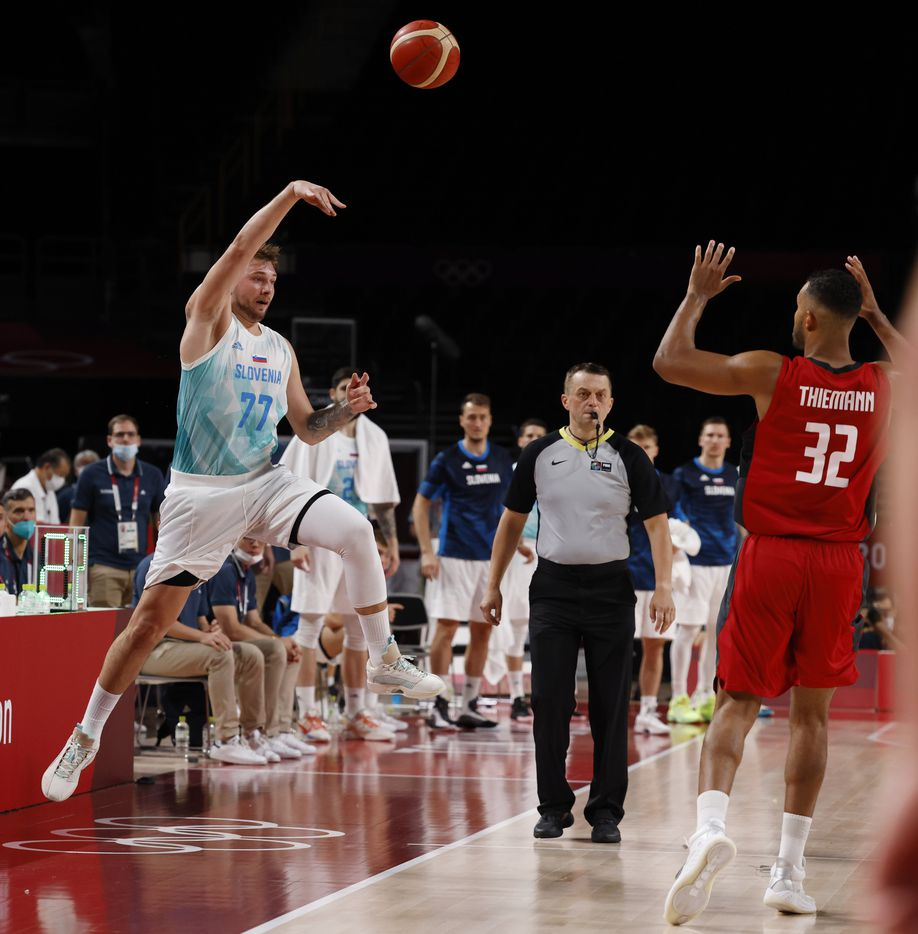 Slovenia's Luka Doncic (77) saves a ball before going out of bounds in front of Germany's Johannes Thiemann (32)   during the second half of play of a quarter final basketball game at the postponed 2020 Tokyo Olympics at Saitama Super Arena, on Tuesday, August 3, 2021, in Saitama, Japan. (Vernon Bryant/The Dallas Morning News)