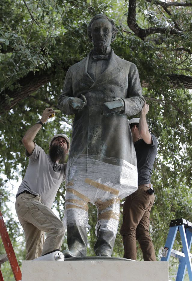 Workers wrap protective materials around a statue of Confederate President Jefferson Davis as they prepare to move the sculpture on the University of Texas campus, Sunday, Aug. 30, 2015, in Austin, Texas. The Davis statue, which has been targeted by vandals and had come under increasing criticism, will be moved and placed in the school's Dolph Briscoe Center for American History as part of an educational display. (AP Photo/Eric Gay) 09012015xPUB