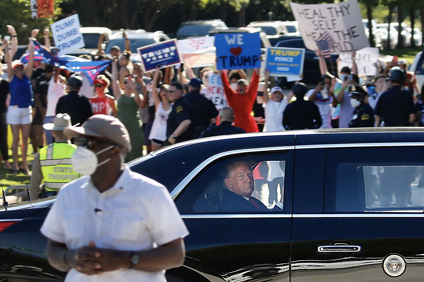 """Supporters and detractors line the road as President Donald Trump rides in """"The Beast,"""" the Presidential limo, on Hillcrest after leaving Gateway Church in Dallas, on Thursday, June 11, 2020. President Trump is in town for multiple events."""