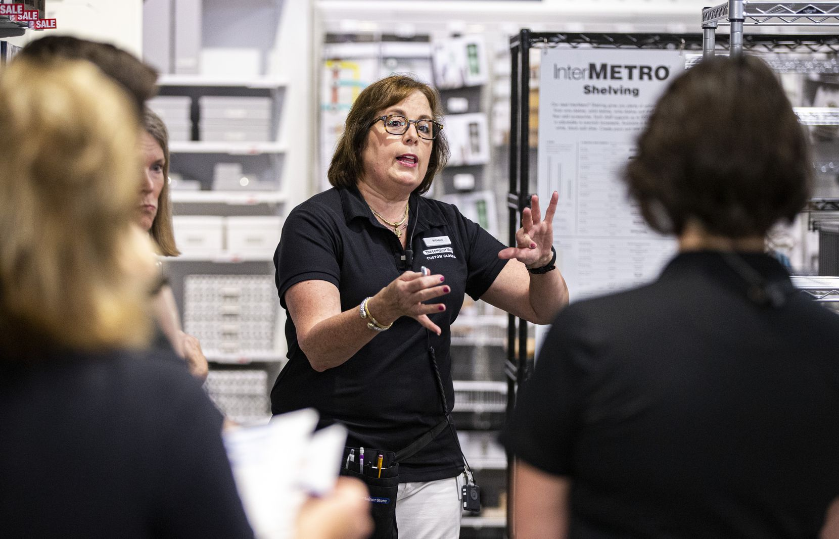Michele McDermett, an employee at The Container Store, explained to coworkers how casters are installed on InterMetro shelves during an employee meeting before the store opened.