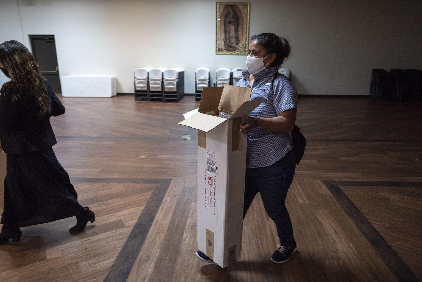 Voluntarios de la iglesia San Juan Diego como Raquel Zárate (izq.) y Ángeles Acevedo llevan los paquetes con ramos de palma que son conservados a temperaturas bajas previo al Domingo de Ramos.