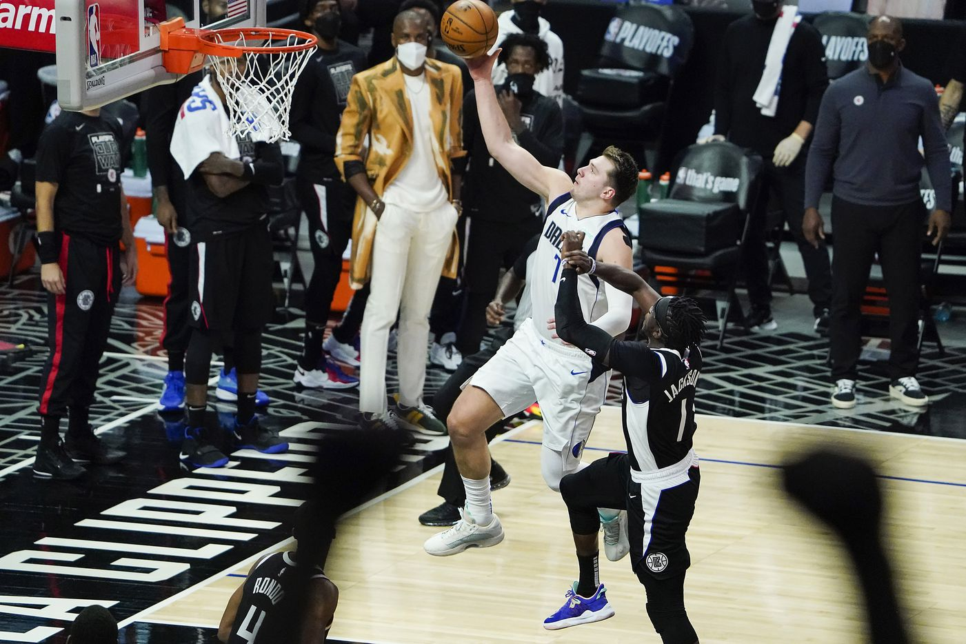 Dallas Mavericks guard Luka Doncic (77) drives for a layup past LA Clippers guard Reggie Jackson (1) during the third quarter of an NBA playoff basketball game at the Staples Center on Wednesday, June 2, 2021, in Los Angeles.  (Smiley N. Pool/The Dallas Morning News)