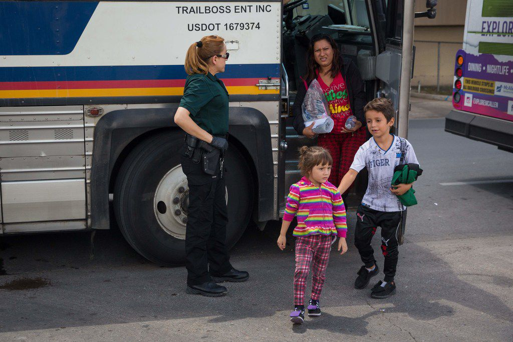 """Immigrants are dropped off at a bus station shortly after being released from detention through the """"catch and release"""" immigration policy on Sunday in McAllen."""