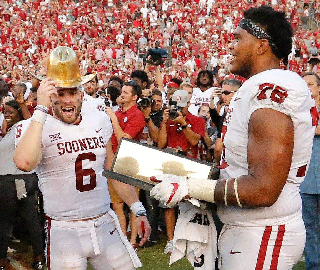 Oklahoma Sooners quarterback Baker Mayfield (6) and Oklahoma Sooners offensive lineman Orlando Brown (78) celebrate with the trophy after the Sooners' 29-24 win during the Oklahoma University Sooners vs. the University of Texas Longhorns NCAA college football game at the Cotton Bowl in Dallas on Saturday, October 14, 2017. (Louis DeLuca/The Dallas Morning News)