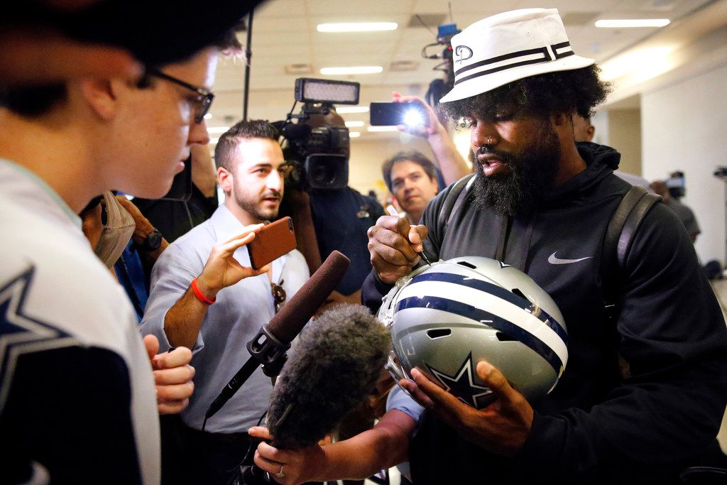 Dallas Cowboys running back Ezekiel Elliott signs a helmet for fan Drew Weinheimer of Prosper, Texas after arriving through customs at Dallas Fort Worth International Airport.  Elliott, who has been holding out for a new contract from the Cowboys, arrived back from Mexico, Tuesday, September 3, 2019. Elliott  (Tom Fox/The Dallas Morning News)