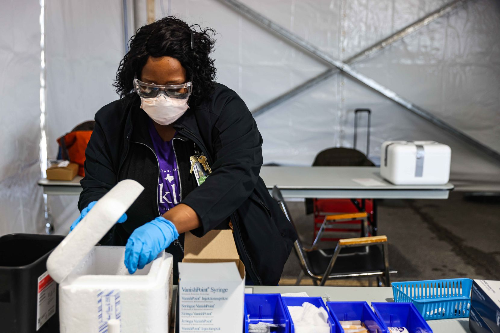 Nurse Lisa Taylor grabs a Pfizer-BioNTech vaccine vial from its container at Ellis Davis Field House, a Parkland testing and vaccine location in Dallas' Red Bird area.