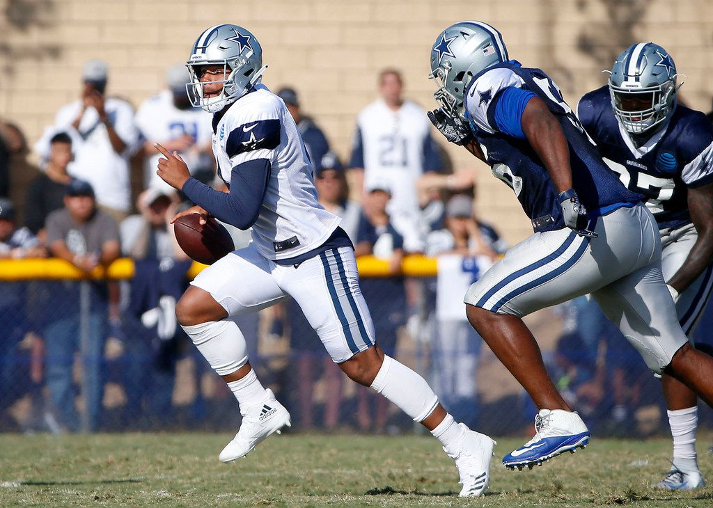 Dallas Cowboys quarterback Dak Prescott, left, scrambles during a scrimmage at the training camp in Oxnard, Calif., Sunday, Aug. 5, 2018. (Jae S. Lee/The Dallas Morning News)