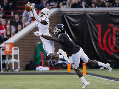 Tulsa cornerback Reggie Robinson II (9) breaks up a pass to Cincinnati wide receiver Malick Mbodj (8) during the second half of an NCAA college football game, Saturday, Oct. 19, 2019, in Cincinnati. (AP Photo/John Minchillo)