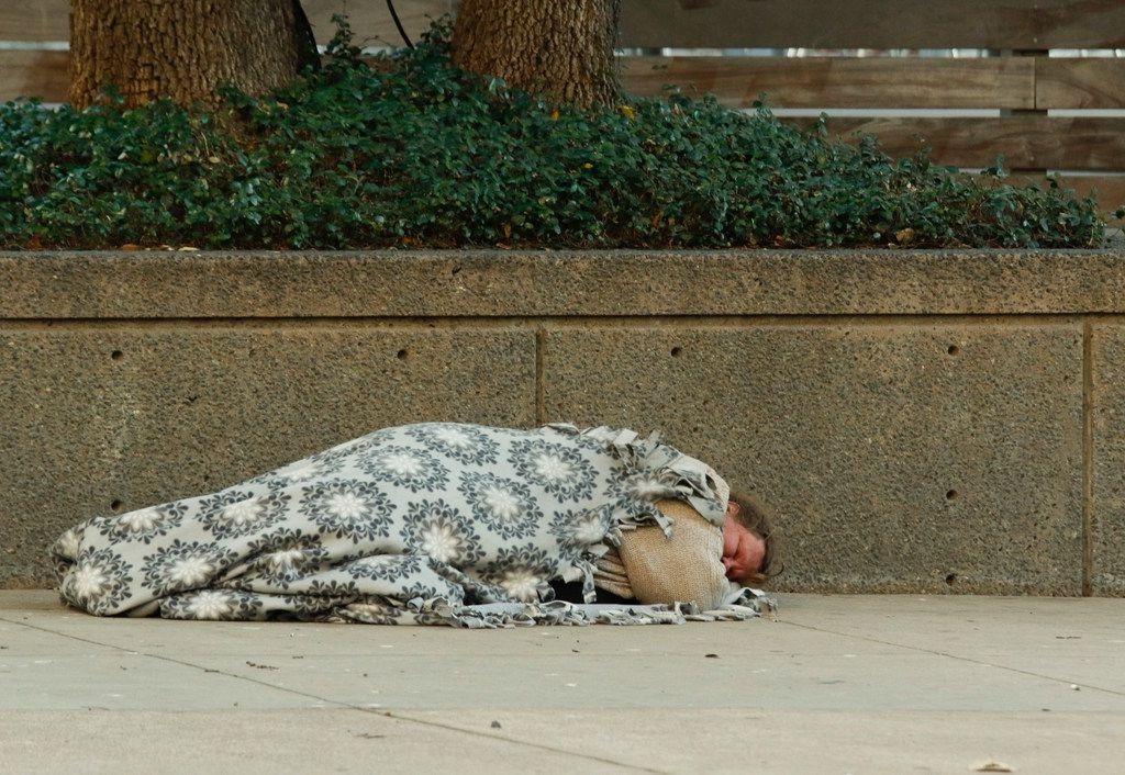 Lisa Kelso curls up under a blanket intersection on St. Paul St. at the intersection of Jackson streets in downtown Dallas Monday, December 11, 2017. She said she has been on the street for about a year. (Ron Baselice/The Dallas Morning News)