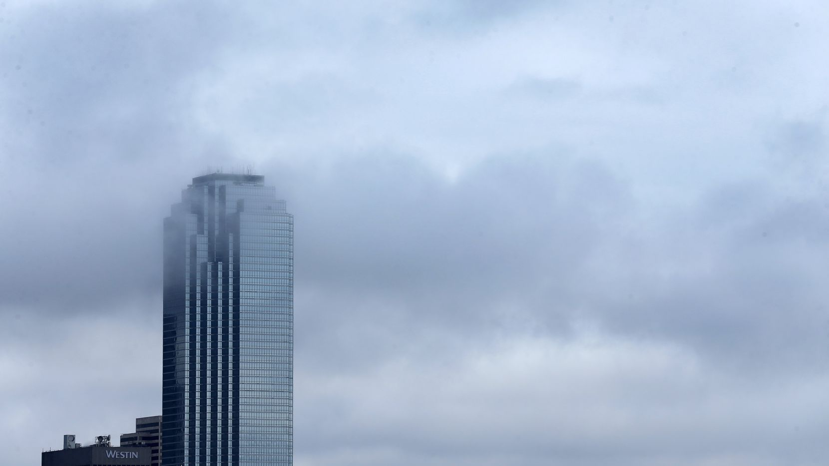 Lingering clouds drifted through the Bank of America building in downtown Dallas as a cold front ushered out the rain on Feb. 24, 2018.