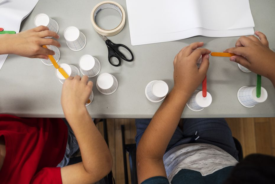 Two young boys use a variety of items such as cups and popsicle sticks to build a bridge as educators with a Perot Museum of Nature and Science Tech Truck teach science lessons to kids at Kleberg-Rylie Recreation Center in Dallas.