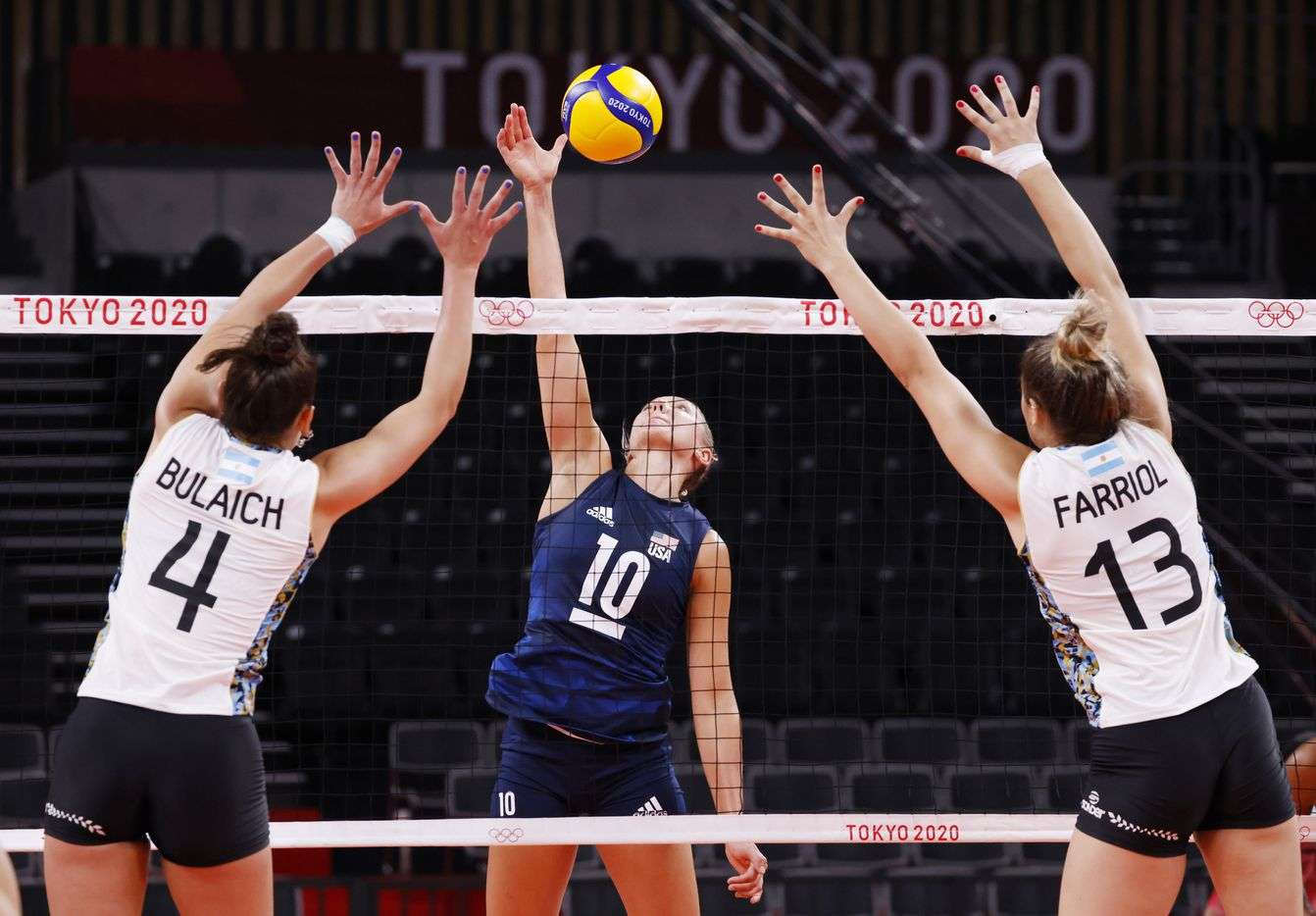 USA's Jordan Larson (10) hits a ball in between Argentina's Simian Daniela Bulaich (4) and Bianca Farriol (13) in a women's volleyball game during the postponed 2020 Tokyo Olympics at Ariake Arena on Sunday, July 25, 2021, in Tokyo, Japan. USA defeated Argentina 3-0 (25-20, 25-19, 25-20). (Vernon Bryant/The Dallas Morning News)