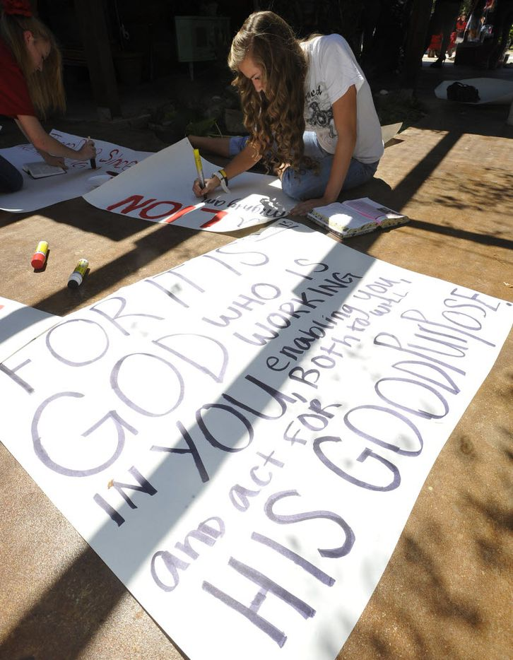In this 2012 file photo, Kountze High School cheerleader Grace Walton works on her sign next to a finished one