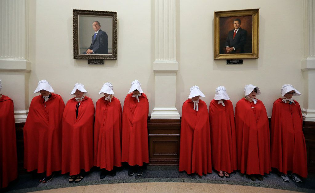 Protesters dressed as characters from The Handmaid's Tale chant in the Texas Capitol Rotunda under portraits of former Texas governors George W. Bush and Rick Perry.