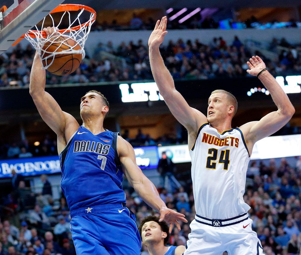 FILE - Dallas Mavericks forward Dwight Powell (7) dunks the ball past Denver Nuggets forward Mason Plumlee (24) in the first half at the American Airlines Center in Dallas, Friday, February 22, 2019.
